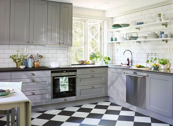 Szarą zabudowę kuchenną zdobią delikatne frezowania oraz metalowe, dekoracyjne uchwyty. Z klasycyzującą zabudową harmonizują białe kafle nad blatem. Fot. Ballingslov, kuchnia Nordic.