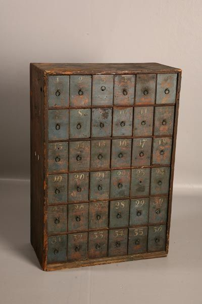 PAINTED THIRTY-SIX DRAWER APOTHECARY CABINET. Early to mid 19th century. Pine. Retains original blue painted drawers, each hand numbered in yellow. Outside of cabinet in old brown paint. 34 1/2'h. 24'w. 12'd.