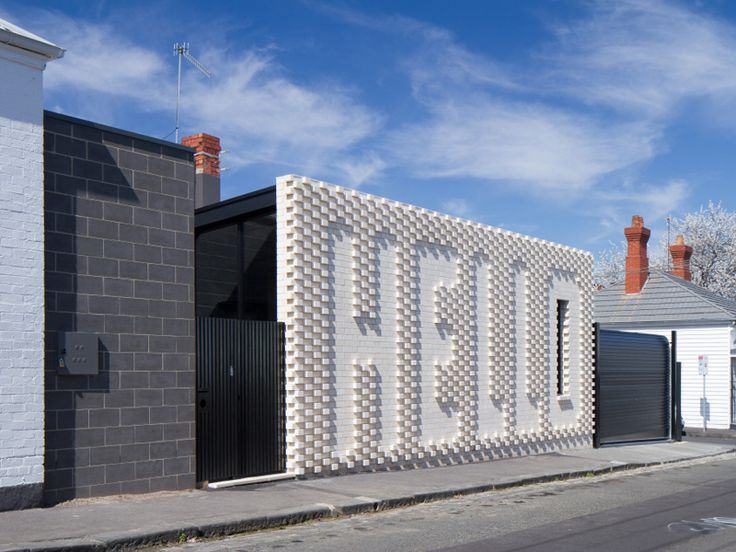 Greeting locals with a large white brick wall that spells out 'HELLO', this home avoids blending in and 'blanding out' of the heritage neighbourhood.   Hello House by OOF! Architects 2014