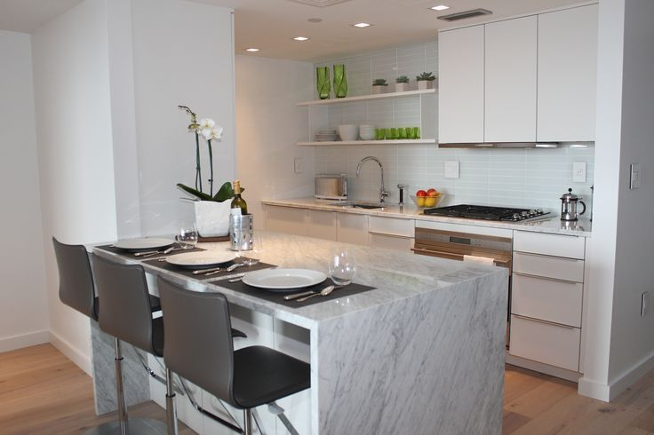 Poggenpohl Boston designed this sleek, modern kitchen in shades of white. #kitchendesign #whiteisback #cookingliving #kitchenisland