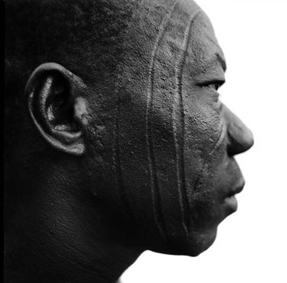 Africa | Man with tribal scarification  Central Burkina Faso.  |  Where inhabitants have dark skin, tattooing has given way to scarificatio. For both men and women in Burkina Faso, scars are marks of beauty signifying passage into adulthood and proclaiming an individual's village, tribe and clan. |  Image and caption © Chris Rainier