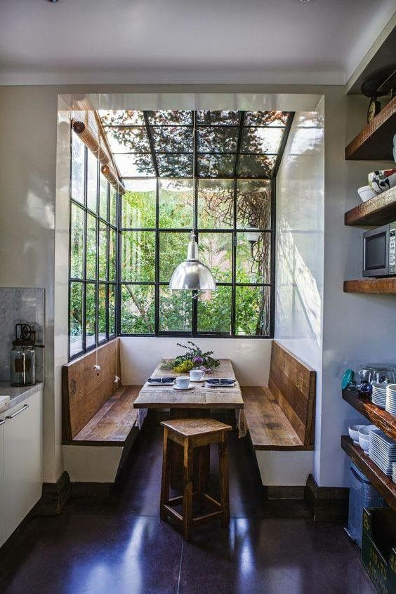 This is a cool way of creating a kitchen diner with built in booth seating around bright and airy windows.