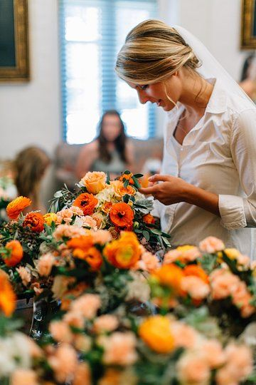 bride looking over her delivered  bouquets of orange, peach dusty blue and cream.