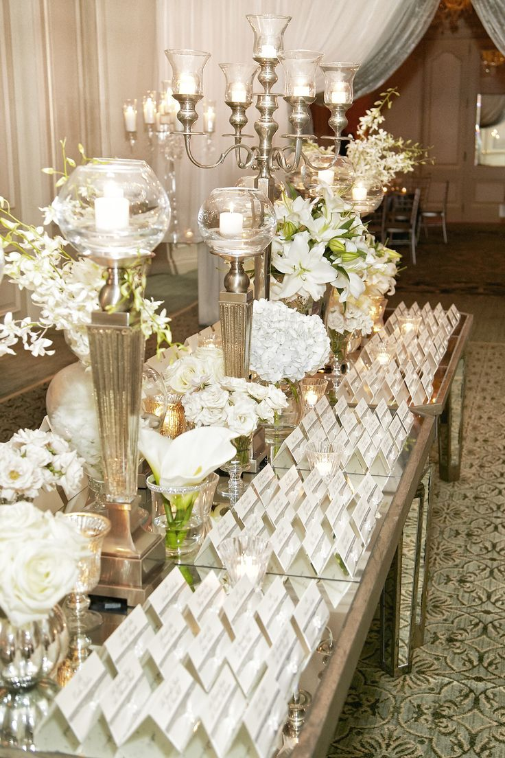 A mirrored table displayed shimmering escort cards, along with silver candelabra and glitter-rimmed arrangements of white florals. #escortcards #candelabra #candles Photography: KingenSmith. Read More: http://www.insideweddings.com/weddings/opulent-chicago-wedding-with-elaborate-decor-entertainment/545/