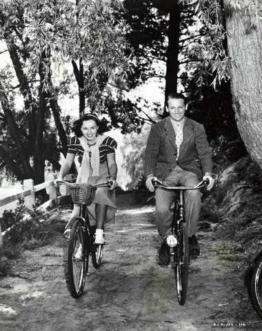 Paulette Goddard and Douglas Fairbanks Jr. ride bikes.    Tags: Douglas Fairbanks Jr., Paulette Goddard, The Young In Heart, MGM, 1938,