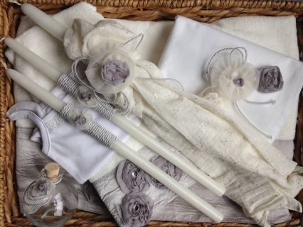"grey and ivory muslin with handmade flowers  baptismal set includes one 21"" lambatha and two 17"" candles, one bath towel, two hand towels, one sheet, a cloth diaper, a cotton onesie, a bottle for oil and a bar of soap.  All items are nicely coordinated and presented in a woven basket.   complimentary shipping on all baptismal sets with candles"