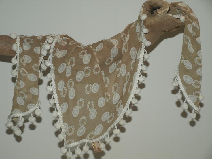 Caramelkleurige sjaal met witte stippen.