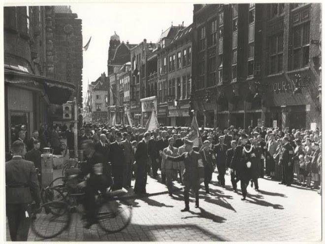 Grote Marktstraat richting Wagenstraat, 8 mei 1945. Op de fiets een verzetsman te herkennen aan zijn armband.