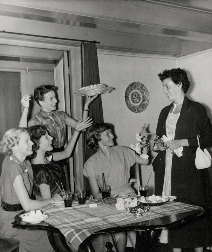 Feestje (verjaardag) in huiselijke kring. Visite  viert feest aan tafel, met taart, bonbons en glazen frisdrank.