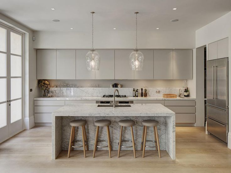 3 Ways To Add Marble In Your Kitchen   Islands, Countertops and Backsplashes   Light grey kitchen cabinets compliment the flecks in the marble and create a sophisticated feel in this bright and airy kitchen.
