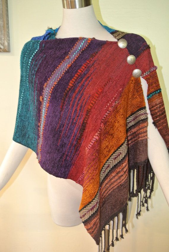 This is a little easy-to-wear southwestern-style ponchito-- meaning a small pull-over poncho. It is very soft and drapey, handwoven in a Saori-style of weaving, which is a free-expression, artistic type of weaving technique. The ponchito is primarily woven in a high-quality rayon chenille yarn with a bamboo warp (the structure yarns of the weaving, which you cannot see.) Bamboo, also, is incredibly soft and luxurious.  I have added 3 silver-tone southwestern concho buttons to the side of the…