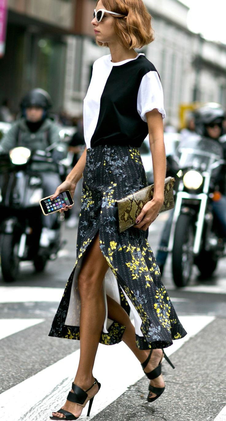 Milan Fashion Week Street Style | A dark floral print midi skirt, styled with a black and white color block t-shirt, python clutch, and white cat eye sunglasses | @stylecaster