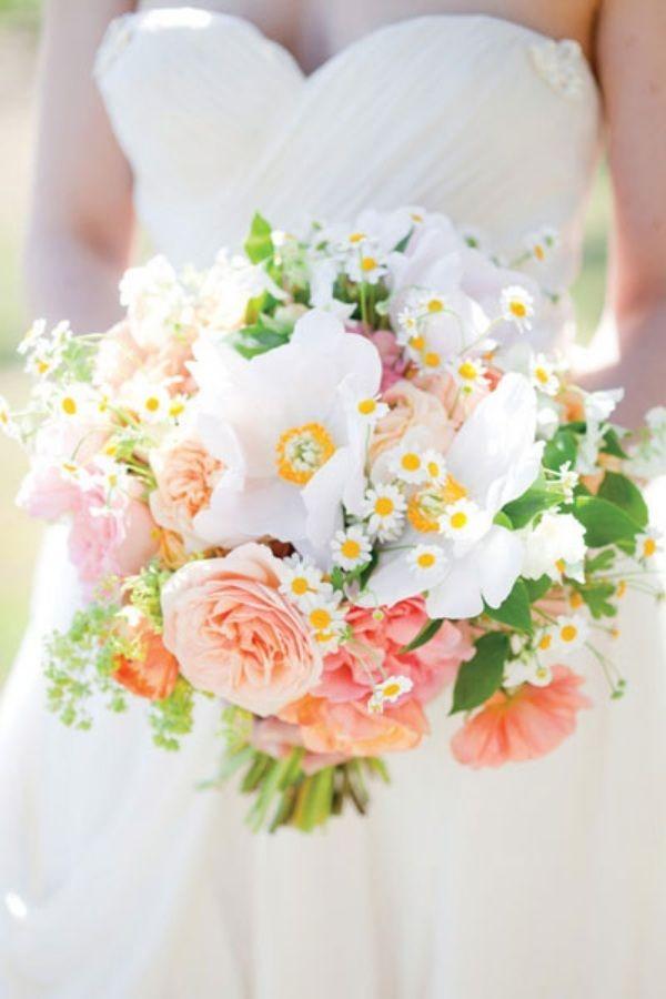 Ein Strauß aus Gänseblümchen, Rosen und grünen Blättern