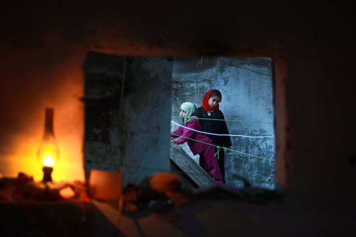 Palestinian girls are seen through a window of their familiy's home during an electricity power cut in the Jabaliya refugee camp, Gaza Strip.