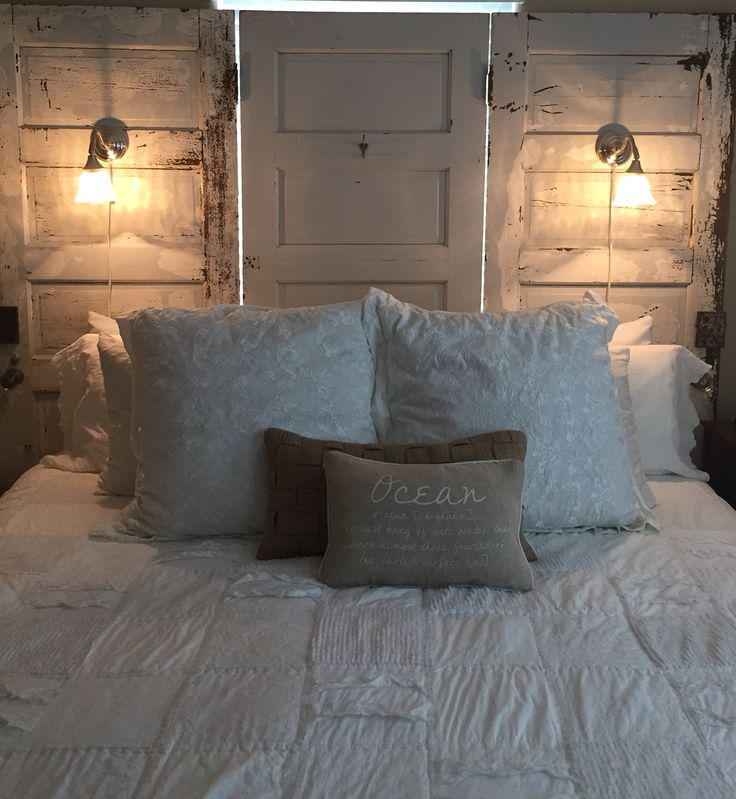 King size headboard made from three salvage doors.  Added also salvage antique door knobs, locks and sconces.