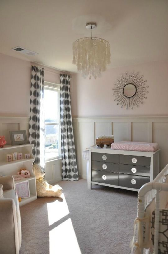 Grey continues to be a hot in the nursery. We spotted this grey nursery in combination with soft pink - a throwback to the 80s but also fresh and modern.    The white background (carpet and walls) keeps the pink and grey color combination from being too cloying. It's a perfect dose of color. Oh, and we have to mention the paneling in the room. It's a great architectural feature for white walls.