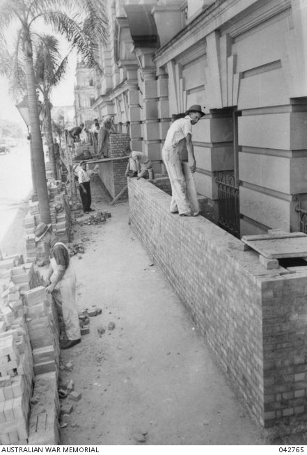 Brisbane, Qld. 18 December 1941. Building a brick screen to protect a building. With the outbreak of the war in the Pacific the work of air raid precautions was accelerated in all States. In the cities plate glass was removed, display windows were boarded up and doorways and windows protected by brick screens or sandbags.