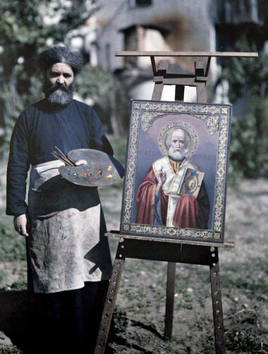 Artist from Mt. Athos stands next to painting of Saint Nicholas, 1920s