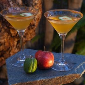 A fall-themed cocktail with apple schapps, feijoa (guava) gin and a caramel-drizzled rim.