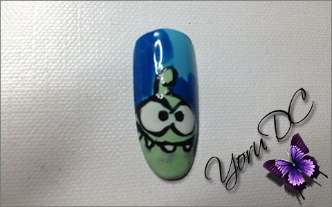 Omnom - Cut The Rope Nail Art.  Materials Used: - Base Coat - Light Blue Nail Polish - Dark Blue Nail Polish - Mint Green Nail Polish - White Nail Polish - Black Striper Polish - Black Nail Art Pen - Top Coat  Tools Used: - Square Tip Detail Brush - Practice Finger Nail Support  Type Nail: - Almond Thumb Nail size 0  Inspiration: http://www.androidguys.com/wp-content/uploads/2013/04/omnom_720.png
