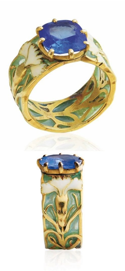 GEORGES FOUQUET - AN ART NOUVEAU SAPPHIRE AND ENAMEL RING, CIRCA 1900. The window enamel band ring applied with gold and white enamel carnations, centring a cushion-shaped sapphire, with French assay mark for gold. Signed G. Fouquet, numbered.