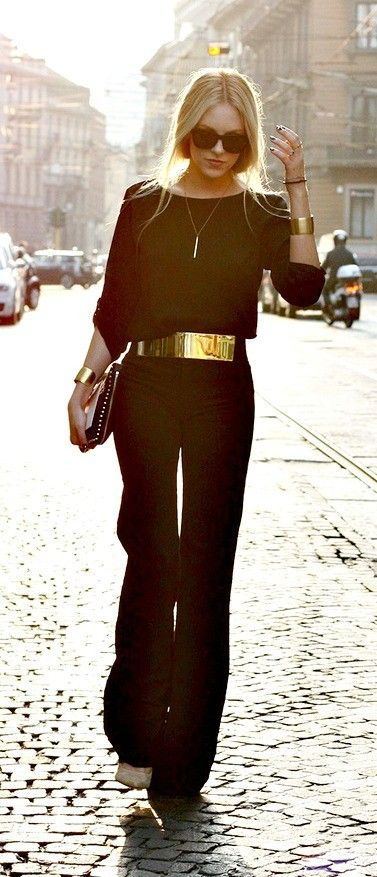Black wide leg trousers with wide gold belt.