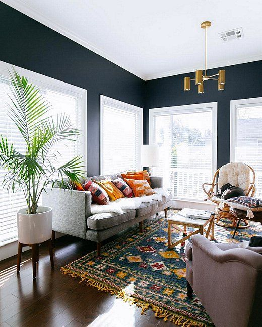 Contemporary midcentury modern living room with a brass chandelier, gray sofa, pops of color on the pillows and rug, and dark navy blue painted walls.