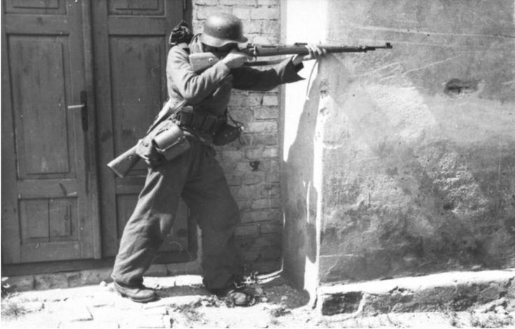 August 1944 - Polen, Warschau.- Warschauer-Aufstand.- Deutscher Soldat mit Gewehr (Karabiner K 98) an Hausecke stehend und zielend