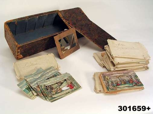 Panorama Viewer, late 1700s, Sweden, rectangular wooden box lined with brown marbled paper. On one side (bottom) a peephole of glass. Inside the box transverse seams (to attach the scenes). Slide Lock. Associated loose rectangularframed mirror and on the back red cardboard with gold print. The glass in the mirror secondary (contemporary glass) 15 pcs envelopes (13 pcs original envelopes of white paper with handwriting, 2 secondary) Each envelope contains 6 scenes. Sweden, Nordiska Museet