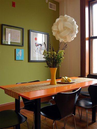 MCM dining area with orange table and avocado walls