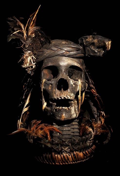 IFUGAO TRIBE HEAD HUNTED SKULL HAT: HUMAN SKULL  BASKET, ANIMAL SKULL HEAD BAND, BAMBOO, FEATHERS.  THE IFUGAO TRIBE, FROM THE PHILIPPINES, PLACE HEAD HUNTED  HUMAN TROPHY SKULLS OUTSIDE OF THEIR HUTS, AS WELL AS,   MOUNT THEM OVER THEIR HEARTHS INSIDE OF THEIR HOMES.