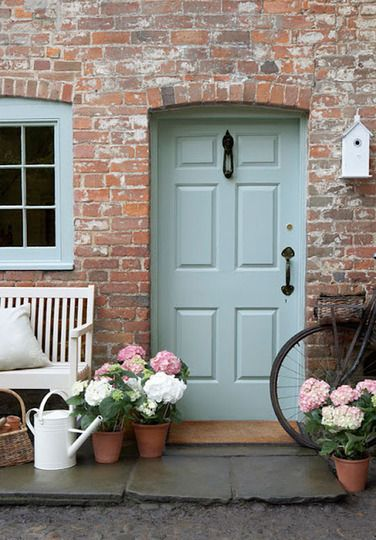Sage green cottage-style door in red-brick building (with hydrangeas in terracotta pots)