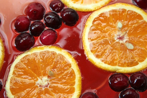 Poinsettia Punch Recipe--8 (1/4-inch-thick) orange slices, from about 2 oranges, for garnish  2/3 cup fresh or frozen cranberries, for garnish  3 cups chilled cranberry juice  3/4 cup chilled Cointreau  2 (750-milliliter) bottles chilled brut sparkling wine or champagne