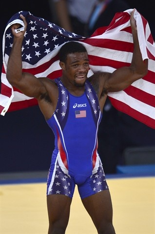 US' Jordan Ernest Burroughs celebrates with national flag after defeating Iran's Sadegh Saeed Goudarzi in their Men's 74kg Freestyle gold medal match.