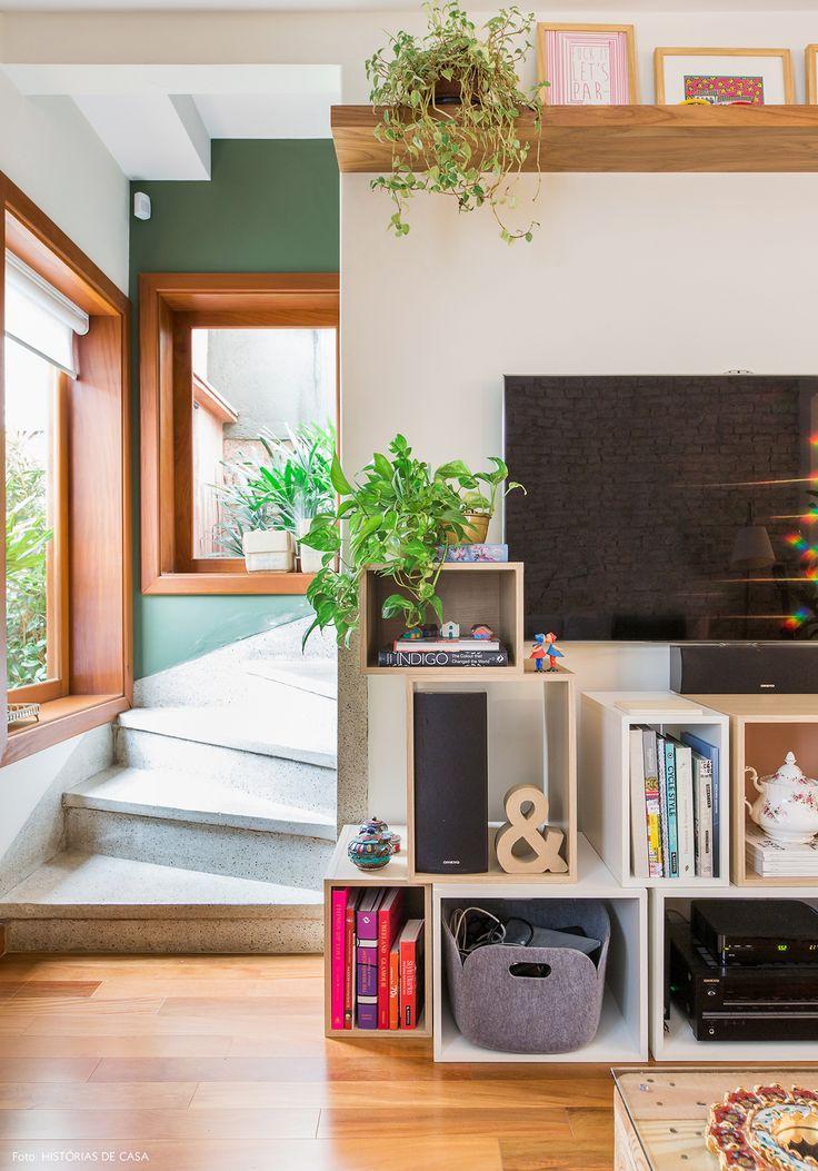 A decoração despretensiosa e acolhedora de uma linda casa de vila com parede de tijolinho, um quintal cheio de plantas e móveis improvisados.
