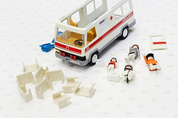 A lot of vintage Playmobil toys from various play sets. We've identified the ambulance from Playmobil set no.3456, 1992. One of the doors is missing on the back, and the one that's left needs some repair in order to fit properly. The top is also missing from the abumlance. The four