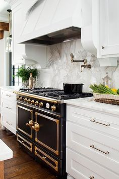 Gorgeous kitchen features white shaker cabinets paired calcutta marble countertops and a calcutta ...