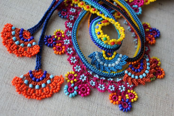Colorful beaded necklace, it is created with orange, indigo, turquoise blue, yellow, magenta pink seed beads and cotton fibers, we used various beaded crocheting techniques.    Three strands in the upper part are crocheted using turquoise blue, indigo blue and orange cotton fiber, and ornamented with seed bead strands and beaded flowery edging in lemon yellow, turquoise, teal blue, cerulean blue, indigo, black and orange tones. We also attached two beaded flowers in the centre, they are…