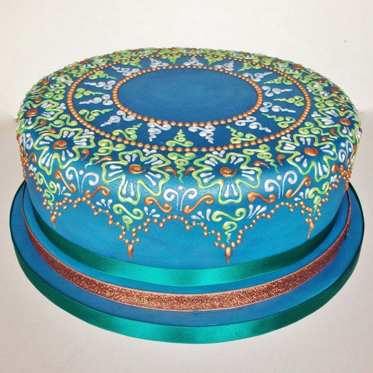 A henna mehndi cake in a palette of green, bronze, gold and pearl white on a blue base.