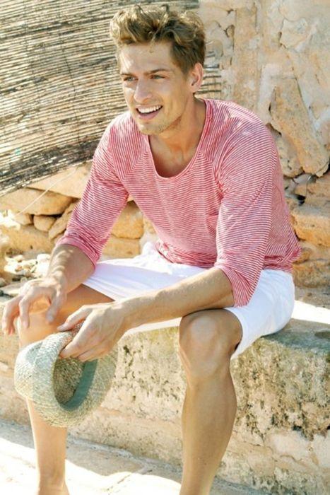 O bluză roz în dungi lângă pantalonii scurți albi se pretează zilelor pe malul mării