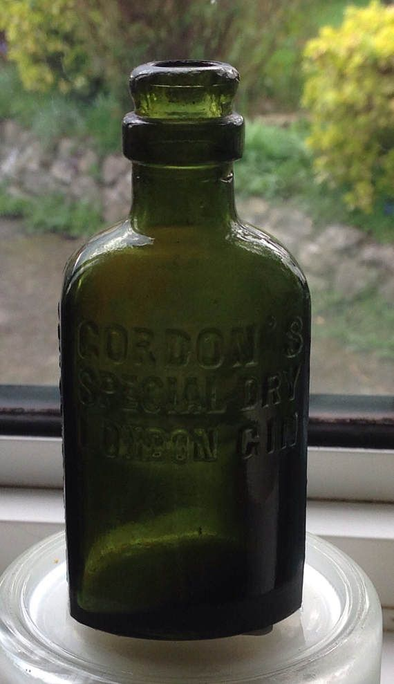 A small dark green antique bottle from the early 1900s, which once contained Gordons Special Dry London Gin.  The bottle is embossed..  GORDONS SPECIAL DRY LONDON GIN on the front.  ESTABLISHED 1769 along each side And has a dragons head with. U C B underneath.  Bottle is 4 tall by 1.5 wide. It has a slight residue mark in the back shoulder area and some tiny nicks in the collar at the top...these are barely noticeable...( please zoom in on photos to see. )  A lovely old bottle ,which looks…