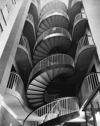"""Figura centrale nella fotografia architettonica, Oscar Savio sapeva riprendere i soggetti con un uso magistrale delle luci e, diversamente da quella che viene considerata la classica fotografia architettonica, sapeva creare luoghi """"impossibili"""" attraverso la distorsione prospettica o la selezione metafisica dell'oggetto."""