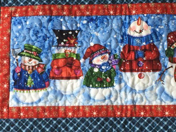 Si vous aimez les bonhommes de neige, puis vous allez tomber en amour avec ce groupe de bonhommes de neige fantaisistes. Ces 6 bonhommes de neige sur le chemin de table tout tout habillé pour la saison des fêtes dans leur rouge, vert un bleu chapeaux, pulls et écharpes. Ils va certainement mettre un sourire sur votre visage.  Détails :  -26,5 x 15 pouces -Fabriqué avec un tissu de qualité 100 % coton -Machine et le matelassage -Double pli reliure cousue vers le bas et cousu main sur le dos…