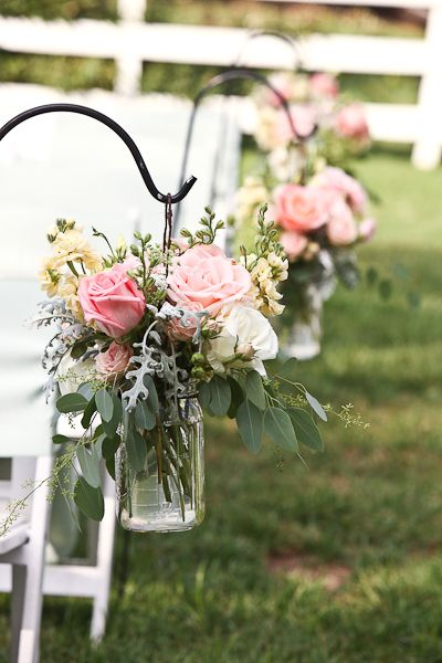 Shepherd hooks and Mason jar bouquets are one way to decorate for the wedding isle