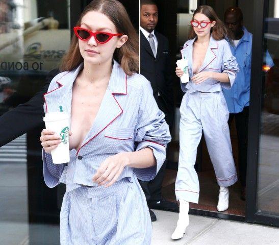 Gigi Hadid  DOVE: New York  LOOK: Da notte. La modella lascia Starbucks in un sexy completo pigiama celeste a righe bordato di rosso Christian Dada e stivali Stuart Weitzman bianchi, completano gli occhiali rossi Le Specs.