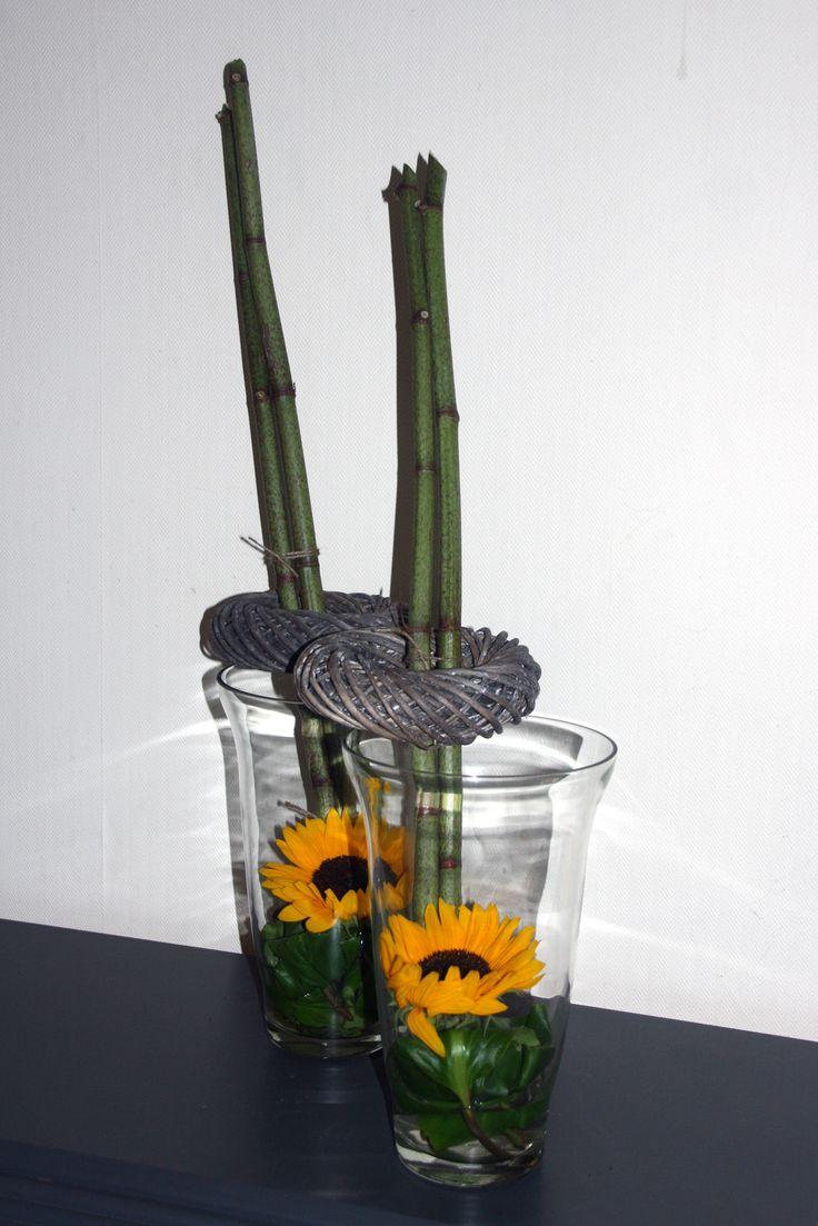 Zonnebloem in vaas met op rand krans en takken.