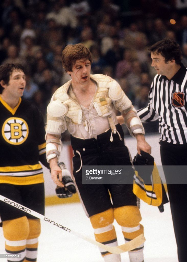 Terry O'Reilly #24 of the Boston Bruins is helped over to the penalty box after being involved in a fight as Brad Park #22 talks with the linesman during a Stanley Cup Quarter-Finals game against the New York Islanders in April, 1980 at the Nassau Coliseum in Uniondale, New York.