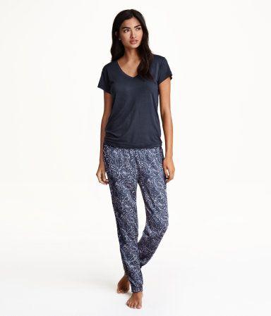 Todelt natsæt i blød viskose. T-shirt i jersey med V-udskæring. Bukser i vævet kvalitet med trykt mønster. Elastik i taljen og smock nederst på benene.