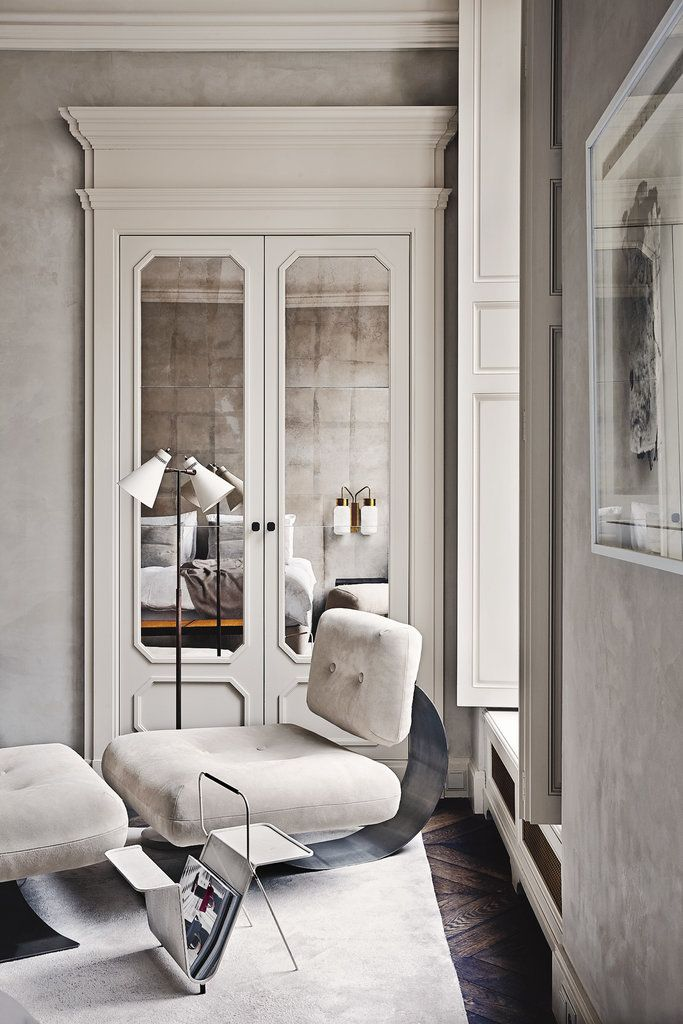 The mirrored closet doors in Joseph Dirend's Parisian apartment reflect the bed and an Azucena sconce.