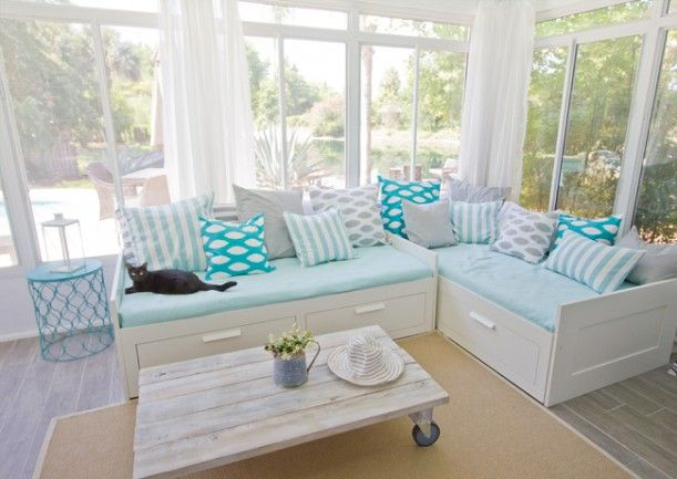 Ikea daybeds, a spraypainted end table (Valspar Exotic Sea), faux-wood tile, and such cute pillows! Love this sunroom makeover.